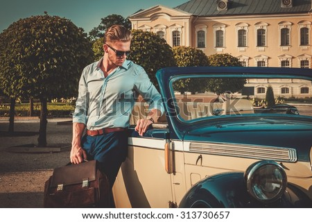 Confident wealthy young man with briefcase near classic convertible  - stock photo
