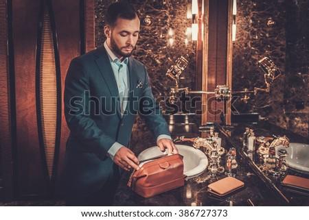 Confident well-dressed man in luxury bathroom interior. - stock photo