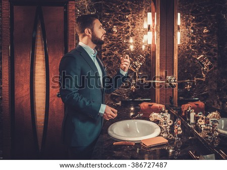 Confident well-dressed man using perfume in luxury bathroom interior. - stock photo