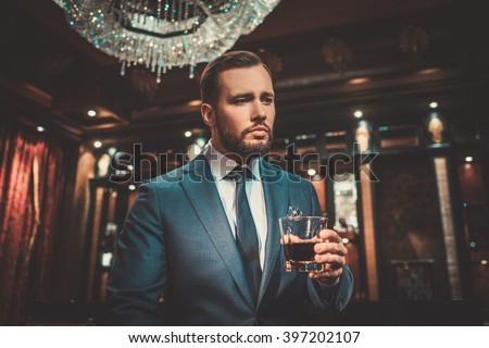 Confident well-dressed man with glass of whisky in luxury apartment interior. - stock photo
