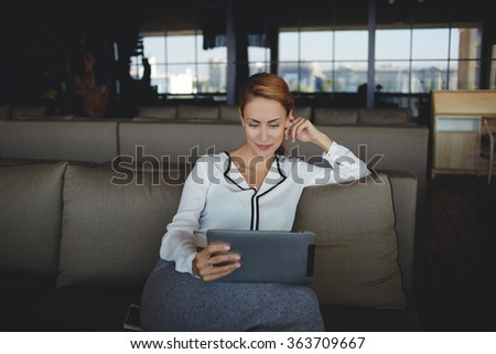 Confident woman ceo reading information on portable touch pad while waiting for start meeting with business partner,young female watching news via network on digital tablet while sitting in restaurant - stock photo