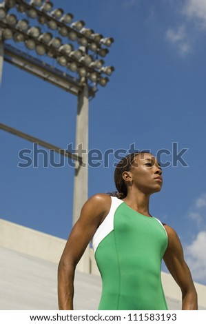 Confident woman in sportswear in front of floodlight looking away - stock photo