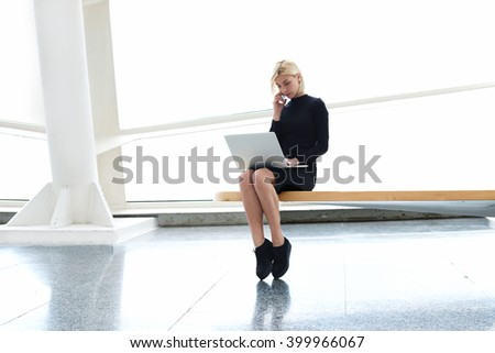 Confident woman skilled managing director having mobile phone conversation with her secretary, while is sitting in modern office interior with open laptop computer during business travel in New York - stock photo