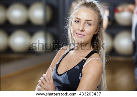 Confident Woman Standing Arms Crossed In Gym - stock photo