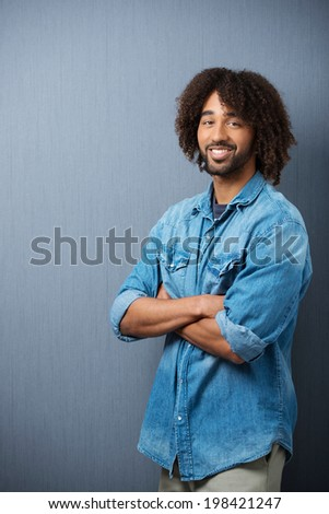 Confident young African American man standing smiling at the camera with folded arms against a grey background with copyspace - stock photo