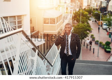Confident young African businessman talking on phone while walking - stock photo