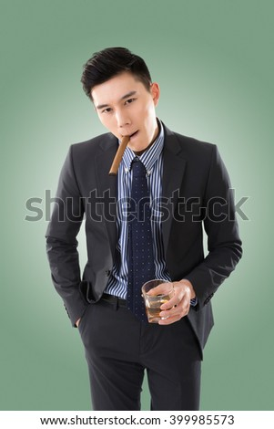 confident young Asian businessman holding a cigar - stock photo