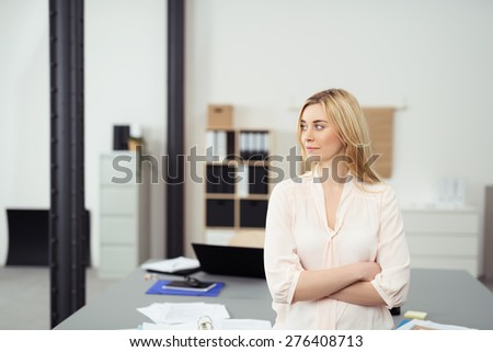 Confident Young Blond Business Woman Standing with Arms Crossed Leaning Against Table in Casual Office Boardroom and Looking to the Side - stock photo
