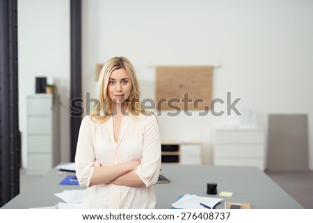 Confident Young Blond Business Woman Standing with Arms Crossed Leaning Against Table in Casual Office Boardroom and Looking at Camera - stock photo