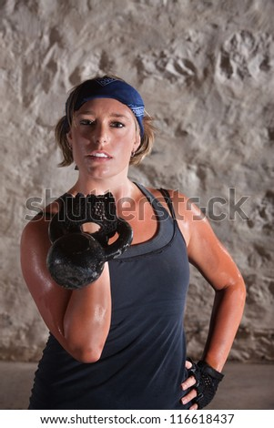 Confident young blonde with hand on hip and kettle bell - stock photo