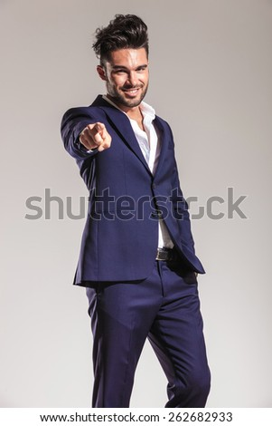 Confident young business man holding one hand in his pocket while pointing at you. - stock photo