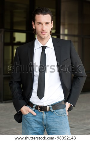 Confident young business man looking at camera. Dark background. - stock photo