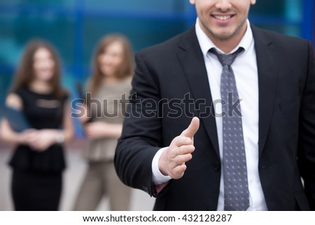 Confident young business man offering hand for greeting or agreement handshake outdoor. Successful Deal Concept. Businesspeople Team on the background. Close-up - stock photo