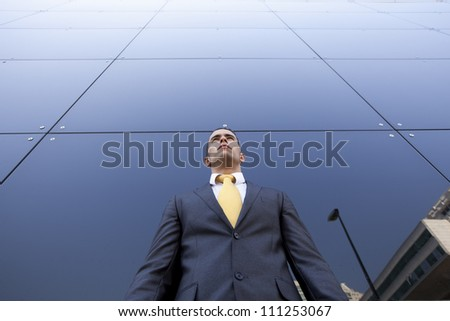 Confident young businessman next to his office building - stock photo