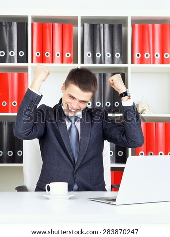confident young businessman triumph looking at laptop - stock photo