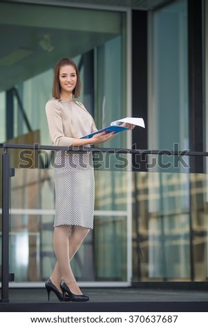 Confident young businesswoman analyzing paperwork in front of her office - stock photo