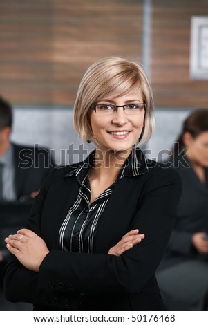 Confident young businesswoman standing in office hallway, arms crossed, smiling. - stock photo