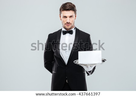 Confident young butler in tuxedo holding blank card on tray - stock photo