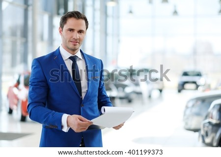Confident young car dealer standing in showroom. - stock photo