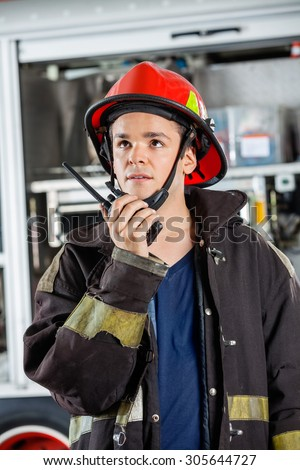 Confident young firefighter looking away while using walkie talkie at fire station - stock photo