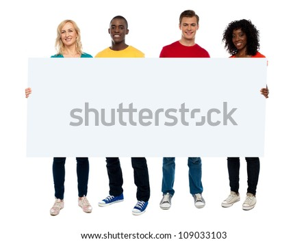 Confident young group showing blank poster, full length portrait - stock photo