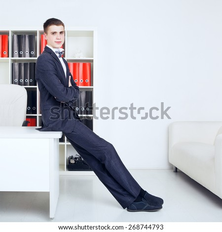confident young handsome businessman in his office - stock photo