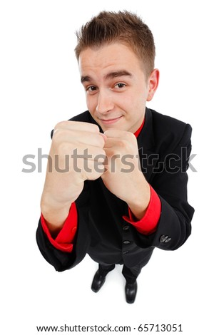 Confident young invincible business man showing fists and smiling - stock photo