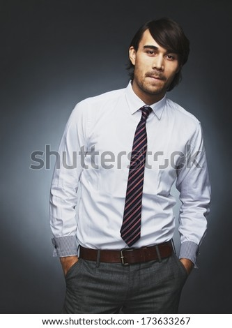 Confident young male executive standing with his hands in pocket. Young businessman looking at camera while standing against black background. - stock photo