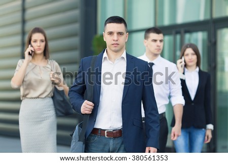 Confident young man in front of the group of busy business people on the move - stock photo