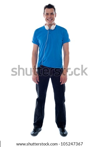 Confident young man standing with headphones around his neck - stock photo