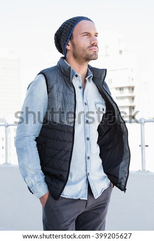 Confident young man wearing beanie hat and jacket - stock photo