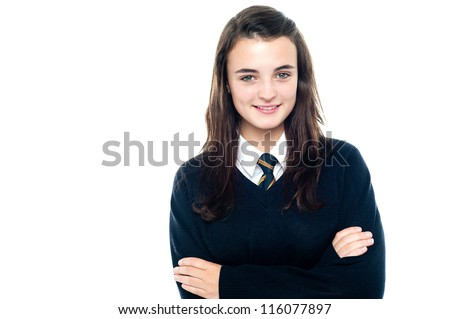 Confident young school child in uniform posing with folded arms - stock photo
