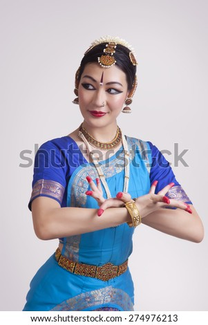 Confident young woman performing classical dance on gray background - stock photo