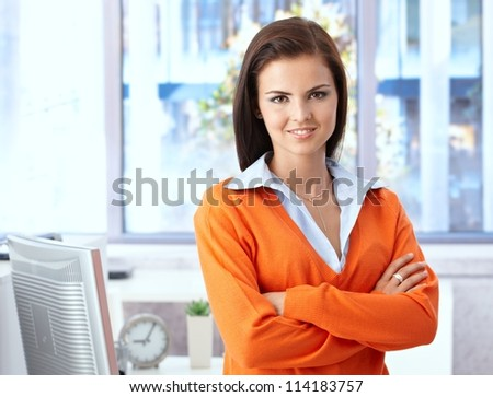 Confident young woman smiling in bright office, looking at camera. - stock photo