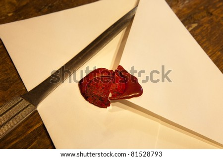 Confidential envelope with a broken red wax seal - stock photo