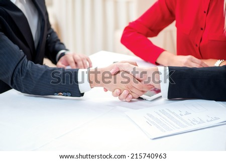 Confirmation of sponsorship. Three successful and confident businesspeople shake hands. Businesspeople in formal attire sitting in an office at a desk close-up view of hands - stock photo