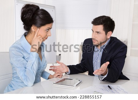 Conflict and problems on workplace: discussing boss and trainee. - stock photo