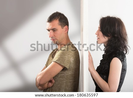 Conflict between man and woman standing on either side of a door - stock photo