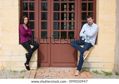 Conflict between man and woman standing on either side of a wall - stock photo