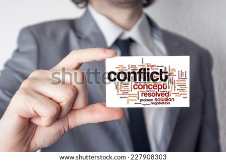 Conflict. Businessman in suit with a black tie showing or holding business card - stock photo