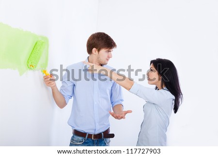 conflict couple, paint in green color white wall of their new apartment home relationship problem, negative emotion, man and woman emotional arguing - stock photo