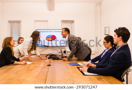 Conflict in the office : Business woman arguing with her boss at meeting over latest sales figures with others watching embarassed - stock photo