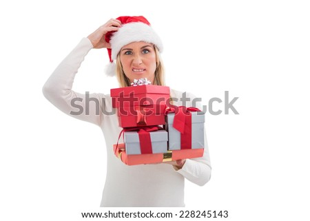 Confused blonde in santa hat holding gifts on white background - stock photo