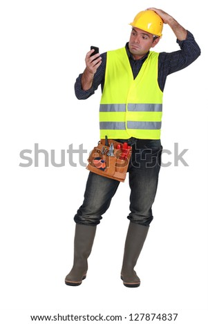 confused builder looking at mobile telephone - stock photo
