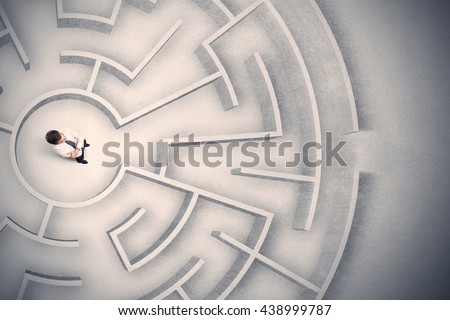 Confused business man trapped in a circular maze - stock photo