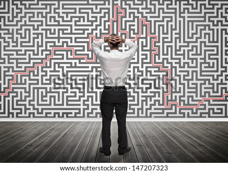 Confused businessman looking at a maze on the wall of empty room - stock photo
