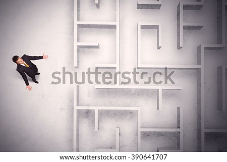 Confused businessman standing at a maze wall with grungy background - stock photo