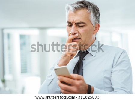 Confused businessman with hand on chin having troubles using a smart phone - stock photo