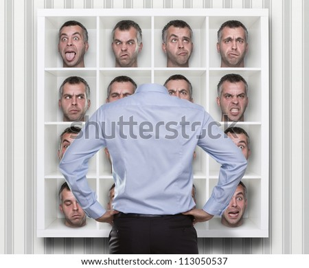 Confused conceptual image, young businessman choosing which face expression to wear - stock photo