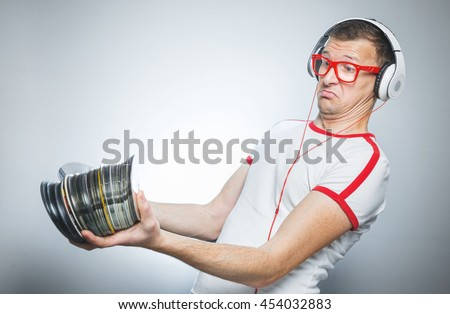 Confused dj holding a lot cds over gray. Studio shot - stock photo